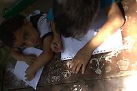 2011 Mokattam Garbage City (alla periferia del Cairo) il quartiere copto dove si vive in mezzo alla spazzatura raccolta: bambini seduti ad un tavolo a disegnare.