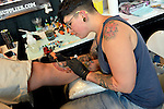 Garden City, New York, USA. September 14, 2014. Tattoo artist DEBORA CHERRYS, from Spain, tattoos the leg of ANTHONY MEISTER, of Seaford, at the United Ink Flight 914 tattoo convention at the Cradle of Aviation museum of Long Island.
