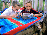 Two young boys with looking at bugs in a bottle with magnifying glass in tree hut.