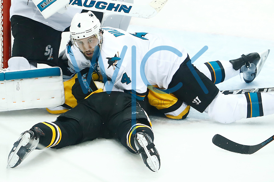 Brenden Dillon #4 of the San Jose Sharks lays on Bryan Rust #17 of the Pittsburgh Penguins in front of the net in the second period during game five of the Stanley Cup Final at Consol Energy Center in Pittsburgh, Pennsylvania on June 9, 2016. (Photo by Jared Wickerham / DKPS)