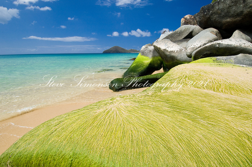 The beach and moss covered beach rocks at Lambert Bay, Tortola, British Virgin Islands