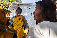 Shanti Adivasi (in yellow saree), 52, shares a joke with villagers as she distributes this week's Khabar Lahariya newspaper in a remote tribal village in Manikpur, Chitrakoot, Uttar Pradesh, India on 6th December 2012.  Shanti used to be a wood gatherer, working with her parents since she was 3, and later carrying up to 100 kg of wood walking 12km from the dry jungle hills to her home to repack the wood which sold for 3 rupees per kg. After learning to read and write in an 8 month welfare course, at age 32, she became a reporter, joining Khabar Lahariya newspaper since its establishment in 2002, and making about 9000 rupees per month, supporting her family of 14 as the sole breadwinner. Photo by Suzanne Lee for Marie Claire France.