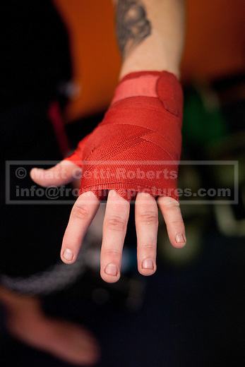 Before a lesson dedicated to practicing the various strikes used during mixed martial arts, a student shows his wrapped hand before donning his gloves.  Due to the nature of the sessions protective equipment is used by MMA students even when learning.