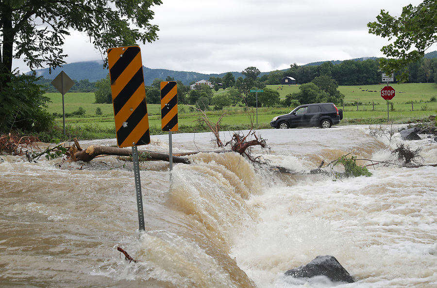 A car drives past heavy flood waters from the South River at the intersection of Octonia Road and South River Road Friday in Greene County. Photo/Andrew Shurtleff Photography, LLC