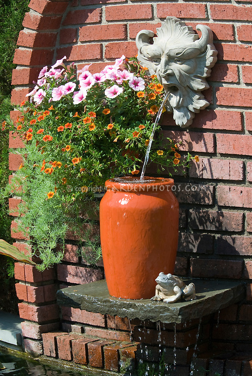 Garden fountain water and ornament on brick wall, with devilish statue character spouting water into urn, with hanging basket of pink flowering petunias and orange calibrachoa, frog ornament, waterfall feature