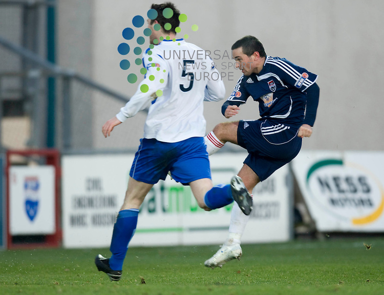 FOOTBALL.Homecoming Scotland Scottish Cup 3rd Round.Ross County v Dumbarton.Ross Co player (dk/blue) Sean Higgins fires home the County opener.Dumbarton player (white) Ben Gordon