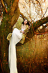 A brunette in a long white gown sitting on a tree in an autumnal forest.