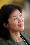Asian woman listening to music, smiling