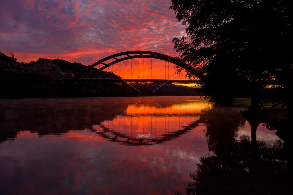 The clouds remind me of lava flowing from volacanic eruption in this image of the 360 Pennybacker bridge during a spectacular sunrise as steam rises over Lake Austin.