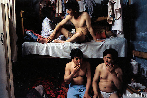 France, Paris, 05-2003..Illegal Chinese at a safe house in Paris. The two men share a bed to cut costs. They are a new wave of immigrants from China?s northeast, home to millions of former cradle-to-grave factory workers laid off by closures. ..