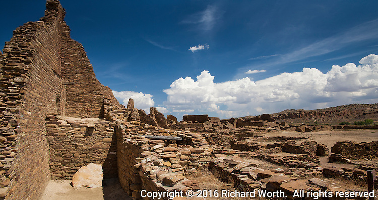 Ancient ruins under today's cottonball clouds and deep blue sky.  History and Current Events
