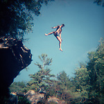 Young man jumping off rock into water