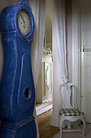 A blue Swedish Mora clock and a Rococo chair in the hall