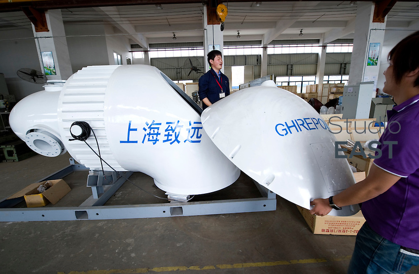 Workers joke while working on a 50 Kwatts wind turbine in GHRE Power factory in Shanghai, China, on June 4, 2010. Photo by Lucas Schifres/Pictobank