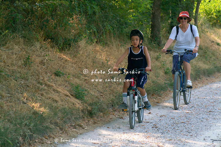 Grandmother and her grandson cycling together on a dirt road, Canal du Midi, Carcassonne, France.