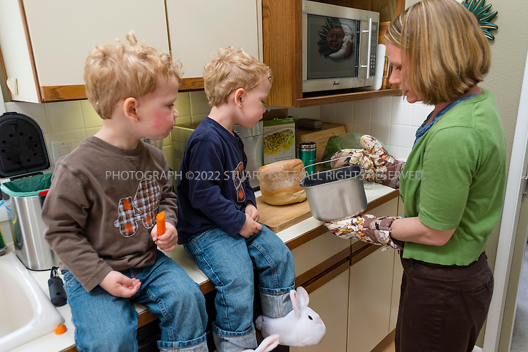 5/29/2012--Seattle, WA, USA..Eden Mack, 39, and her 2 yr old twins, Adrian (blue shirt) and Anderson (brown shirt) in their home in Seattle, WASH. Mack's children suffer from serious allergies to eggs and nuts. ..Here, Eden feeds her twins a pre-dinner snack of raw vegetables while making home made bread. For dinner they will eat talipia. brown rice and broccoli...©2012 Stuart Isett. All rights reserved.