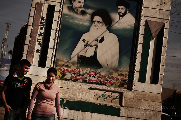 Baghdad, Iraq  : Thur 4rd Dec 2009 :..Two young Iraqis pass an imposing  Sadrist poster in East Baghdad's  Ghadeer neighbourhood. A recent Prime Ministerial decree shutting down Iraq's nightclubs has raised fears about Iraq's secular future. ..Ayman Oghanna For The Observer