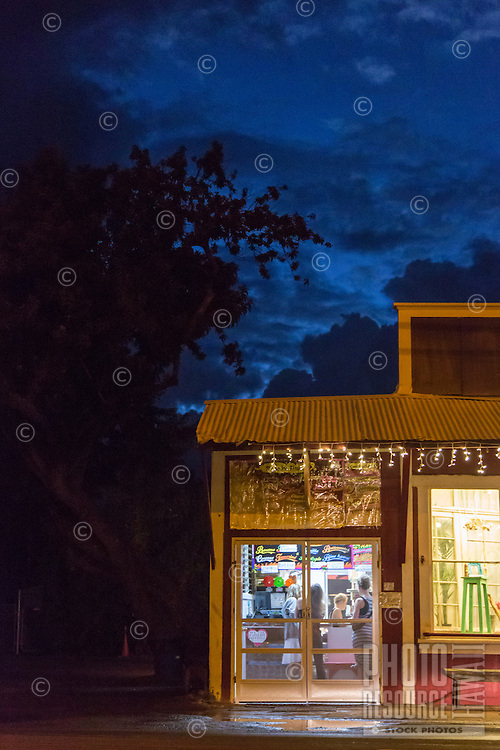 A night scene of tourists in a shave ice store in Hale'iwa Town, North Shore, O'ahu.