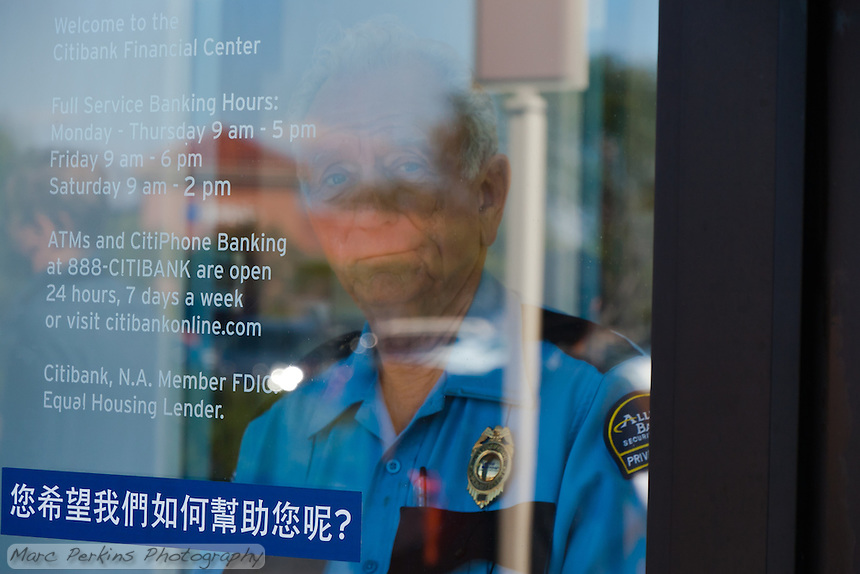 Charles, a security guard at a Citibank in Irvine, CA, warily watches through a locked door as protesters from the Occupy Orange County, Irvine camp march in front of his bank.