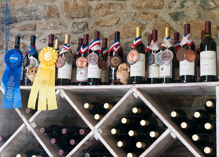 Award-winning bottles are displayed atop the racks of wine for sale at Hillsborough Vineyards' bar.