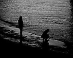 A silhouetted couple on a beach during a winter's sunset. The woman crouching down touching the water on the sand.