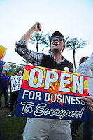 Phoenix, Arizona (February 25, 2014) - A demonstrator holds a sign showing his opposition to Senate Bill 1062. Arizona's Senate Bill 1062 is galvanizing the LGBT community and other civil and religious groups in the state. A crowd rallied in front of Arizona's Capitol in Phoenix to continue pressuring governor Jan Brewer to veto what they call a discriminatory bill. If approved, SB1062 would amend the existing Religious Freedom Restoration Act, which will allow business owners to deny service to gay and lesbian customers so long as proprietors were acting solely on their religious beliefs. As of this protest, the SB1062 is on Brewer's desk awaiting her approval or veto. Photo by Eduardo Barraza © 2014