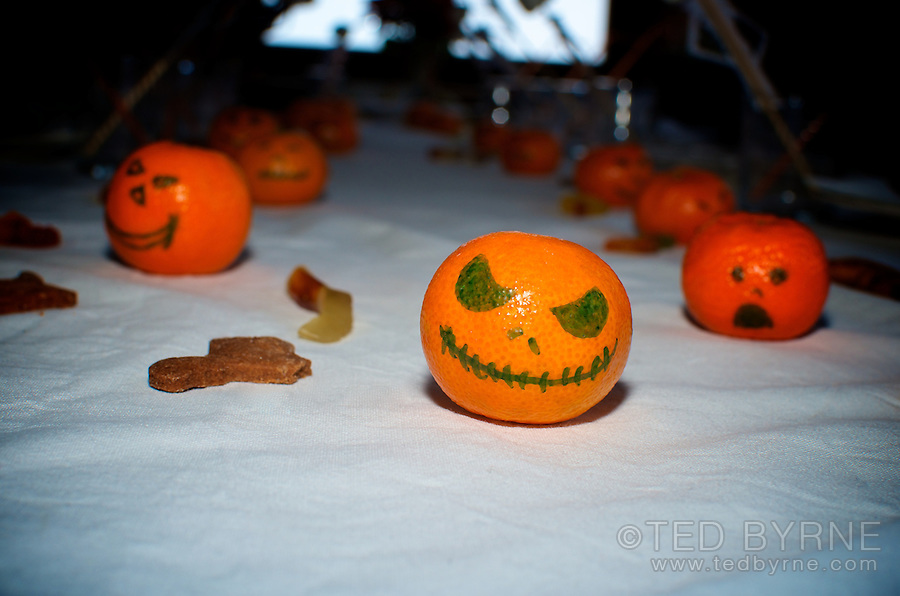 Tangerines with halloween pumpkin faces drawn on them