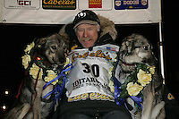 "2006 Iditarod champion Jeff King at the finish line in Nome with his lead dogs ""Salem"" left and ""Bronte"" right."