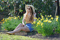 Natasha Jenkins enjoys the unusually warm weather by daffodils in Singleton Park, Swansea, Wales, UK. Monday 25 February 2019
