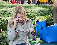 A visitor to Bryant Park in New York on her mobile phone with her iPad on the table on Tuesday, October 29, 2013.  (© Richard B. Levine)