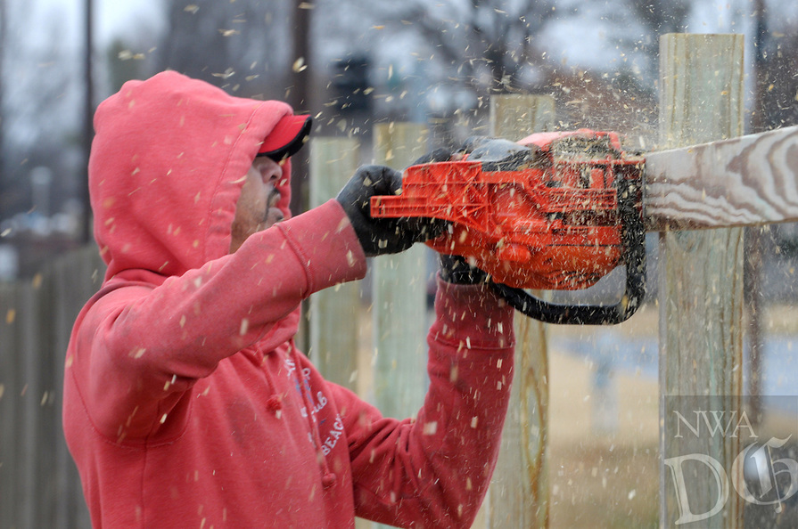 Democrat-Gazette/DAVID GOTTSCHALK Carlos Serrano, a sub contractor, trims Friday, January,4, 2018, post on a new section of fence on the perimeter of the First Assemble of God in Springdale. Serrano would place the frame and then trim the lumber to size with a chainsaw.