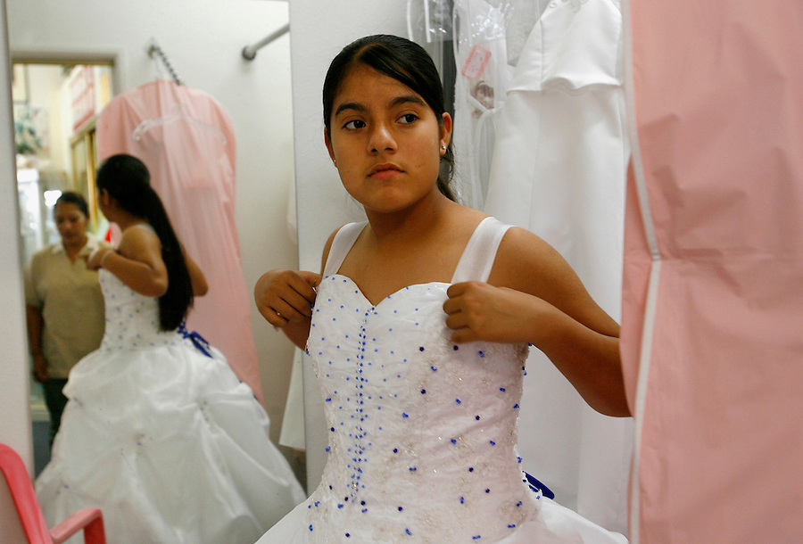 """Elizabeth Ureña, of Indio, trys on the dress for her upcoming quinceañera in the fitting room as her mother looks on. """"I am not used to a big dress like this,"""" says Ureña."""