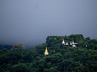 Stupas in the jungle surrounded by Mountains and shrouded by low clouds during a approaching rain storm, near Pindaya, Shan State, Myanmar
