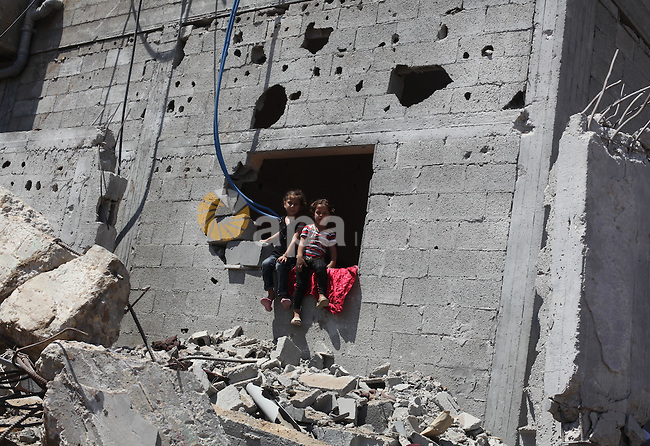 Palestinian children sit on the rubble of their house that witnesses said were destroyed in an Israeli offensive, after a ceasefire was declared in the Shejaia neighbourhood, east of Gaza City. September 6, 2014. Calm returned to the coastal enclave in a August 26 ceasefire, and Gazans were gradually starting to rebuild their lives after a bloody and destructive 50-day war, the deadliest for years. Photo by Ashraf Amra