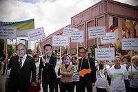 """Aktivisten stehen am Montag (27.05.13) in Berlin waehrend einer Internationalen Konferenz"""" Elektromobilität bewegt"""" mit Transparenten und Masken die die Bundeskanzlerin zeigen vor der Veranstaltungshalle. Foto: Timur Emek/CommonLens"""