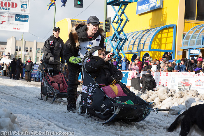 Allen Moore and team leave the ceremonial start line with an Iditarider at 4th Avenue and D street in downtown Anchorage, Alaska during the 2015 Iditarod race. Photo by Jim Kohl/IditarodPhotos.com