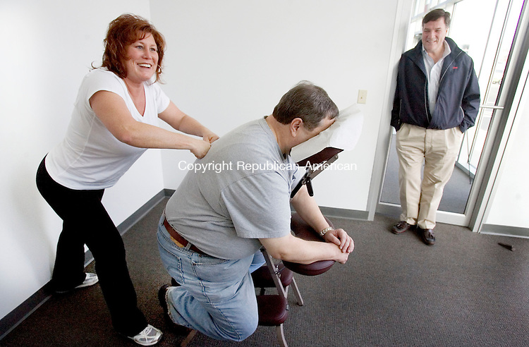 MIDDLEBURY, CT. 20 February 2012-021812SV13-Deborah Stordy, massage therapist, gives Chuck Pagano of Waterbruy a massage while he waits for his car to be serviced at County Line Auto in Middlebury Monday. Bob Bannon, owner, at right, checks in with the customer.  County Line Auto in Middlebury opened a new service center that will contain a little something extra for customers. Every day, customers will be able to take advantage of a different service provider like a massage therapist, a manicurist, a fortune teller, a caricature or portrait artist, a tax accountant, while waiting for their car to be serviced..Steven Valenti Republican-American
