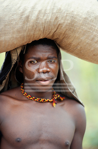 Lulimala, Zambia. Young man carrying a full sack on his head, wearing a plaited red, yellow and black necklace.