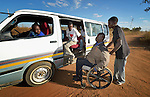 Dominik Tengani begins to enter a kombi near his home in Kuwadzana, Zimbabwe. Tengani is vice chair of the Spinal Injuries Association of Zimbabwe, which supports and advocates for the rights of people living with spinal injuries. He says doctors have been unable to diagnose the cause of his medical condition. He uses an appropriately-designed and fitted wheelchair provided by the Jairos Jiri Association with support from CBM-US. Yet kombi drivers often refuse to allow people in wheelchairs to ride, or charge them extra for taking their wheelchair along.
