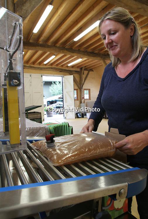 Foto: VidiPhoto..ZOELEN - Appeltjes voor de dorst. Letterlijk. Bij Mobipers in Zoelen rijden particulieren woensdag af en aan om hun eerste zomerappels te laten persen voor appelsap uit eigen boomgaard. Het zijn vooral oud-Nederlandse rassen, meestal van hoogstambomen, die Mobipers nu verwerkt. Het persen van eigen sap is een enorme hype aan het worden. Ook fruittelers komen steeds vaker met een deel van hun oogst naar Zoelen om vers appelsap van eigen 'bodem' te laten persen voor verkoop aan huis. Fruittelers profiteren hiermee naar de stijgende vraag naar streekproducten bij consumenten. Mobipers is het enige bedrijf in Nederland dat appels van particulieren verwerkt tot sap.