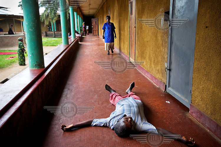A patient at a psychiatric hospital lies on the floor. Many of the people being living here have been abandoned by their families and a lack of drugs means patients are often untreated.