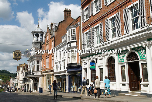 Guildford Surrey UK. High Street shoppers. The Guildhall with orrnate 17th century clock and cupola.