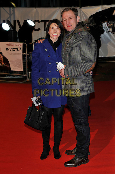 "GUEST & NEIL BACK .Attending the ""Invictus'"" UK Film Premiere at the Odeon West End cinema, Leicester Square, London, England, January 31st, 2010..arrivals full length blue coat black bag boots pinstripe grey gray jacket blazer arm around couple .CAP/PL.©Phil Loftus/Capital Pictures"