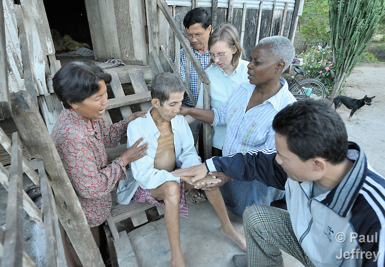 United Methodist mission personnel join with local church leaders to pray for a sick man in the Cambodian village of Pheakdei. The missionaries work with the Community Health and Agricultural Development program of the Methodist Mission in Cambodia.