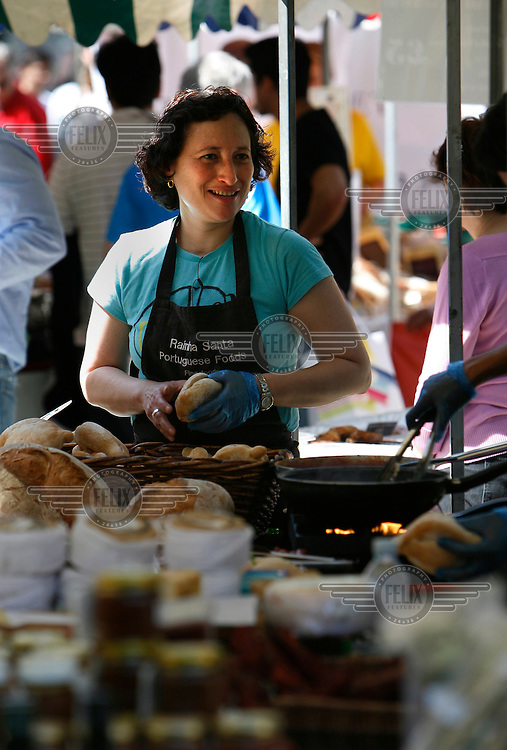A woman cooking portugese foods prepares a bun at Partridges Market on Duke of York Square, Chelsea, London. Partridges is a weekly market which showcases and supplies the best of diverse British foods...