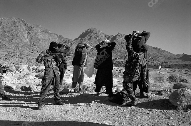 Afghan men are searched for weapons as US and Afghan soldiers search for Taliban just outside of Gonbaz village, Shawali-Kot, Kandahar Province, October 2005.