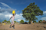 A Dinka woman carries water in the Rhino Refugee Camp in northern Uganda. As of April 2017, the camp held almost 87,000 refugees from South Sudan, and more people were arriving daily. About 1.8 million people have fled South Sudan since civil war broke out there at the end of 2013. About 900,000 have sought refuge in Uganda. <br /> <br /> The Global Health Program of the United Methodist Church has supported work to improve access to safe drinking water in the camp.