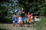 Deaconess Maria Jessica Cicillo high-fives as she walks with a group of children in Mt. Heights, Philippines, where she works as a Christian educator for a nearby United Methodist Church. She is a graduate of Harris Memorial College.