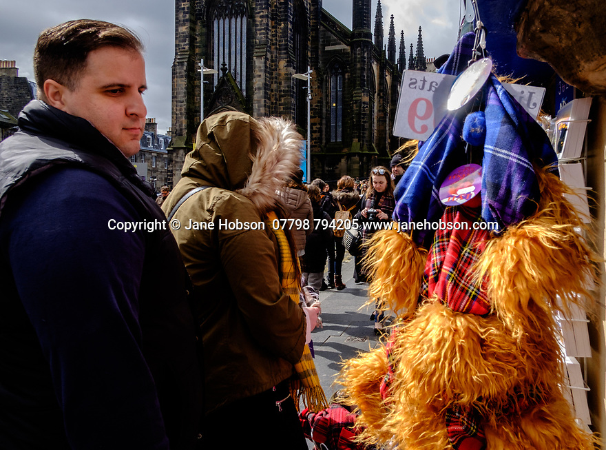 "Edinburgh, UK. 15.04.2017. A man looks at a string of ""Jimmy"" hats, hanging outside a shop on the Royal Mile. Photograph © Jane Hobson."
