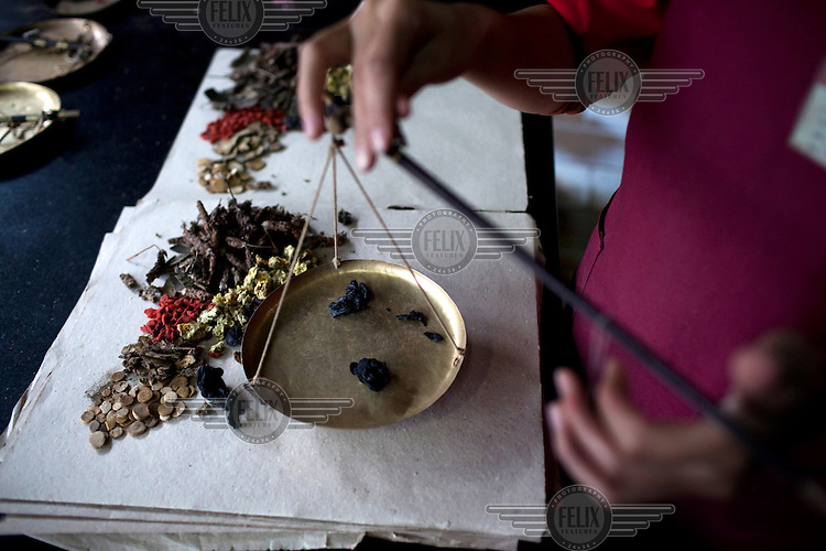 An employee of a Fu Lin Tang Traditional Chinese Medicine shop in Kunming, Southern China, weighs out ingredients.